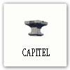 Capitel con volutas en los cuatros extremos, tiene una cara en el medio de cada lado -dentro de una roca-.